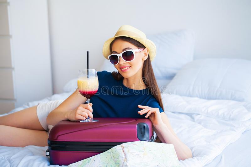 Schönheit mit Cocktail und Koffer auf Bett in hootel Raum lizenzfreies stockbild