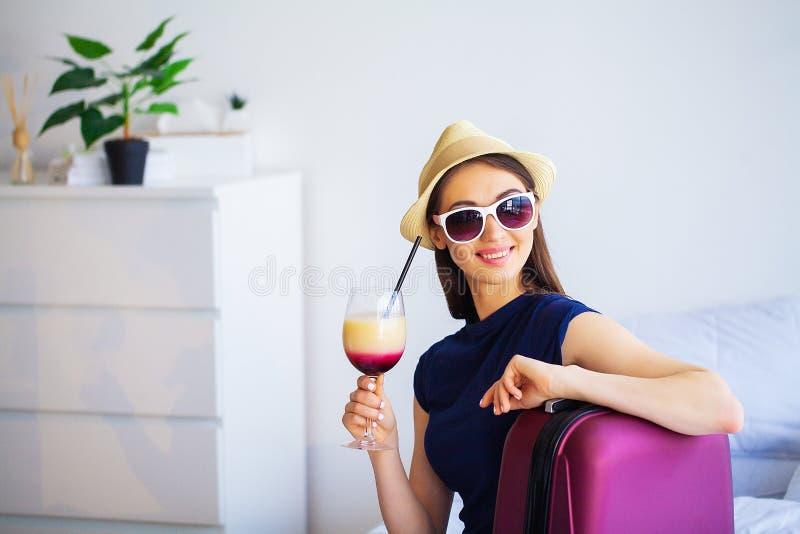Schönheit mit Cocktail und Koffer auf Bett in hootel Raum lizenzfreies stockfoto