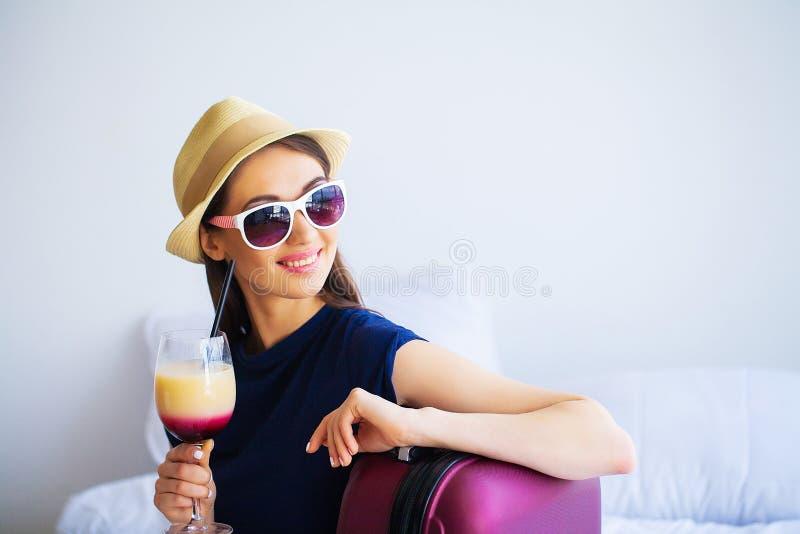 Schönheit mit Cocktail und Koffer auf Bett in hootel Raum stockfoto