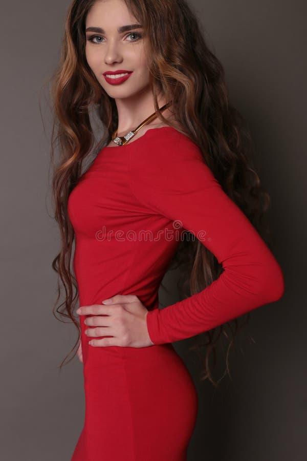 Schönheit Mit Dem Dunklen Gelockten Haar Trägt Elegantes Rotes Kleid ...