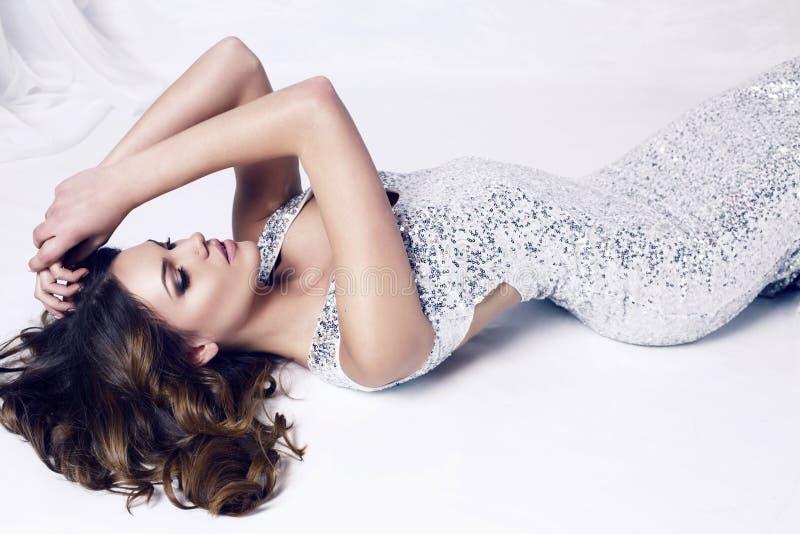 Schönheit mit dem dunklen Haar, das luxuriöses silbernes Kleid trägt lizenzfreie stockbilder