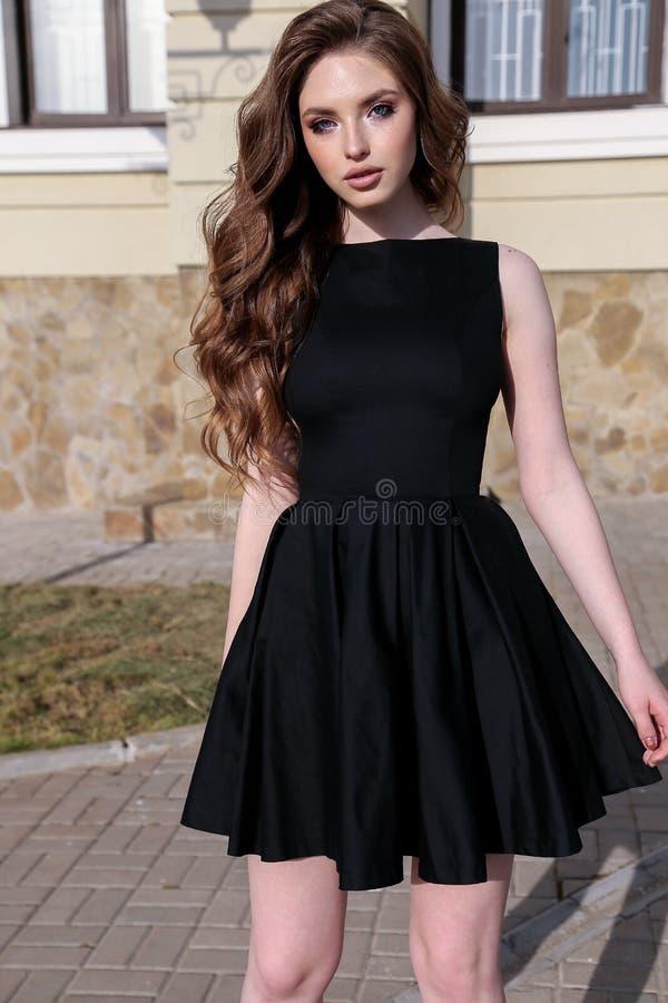Schönheit mit dem dunklen Haar im eleganten Kleid gehend auf das s stockbild