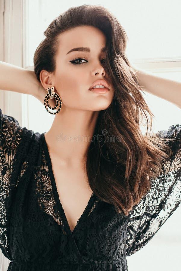 Schönheit mit dem dunklen Haar im eleganten schicken Spitzekleid stockfoto