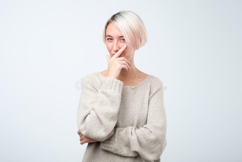 Schönheit mit dem gefärbten kurzen Haar, das Hand unter dem Kinn beabsichtigt, heiklen Plan zu verwirklichen halten schaut lizenzfreies stockfoto