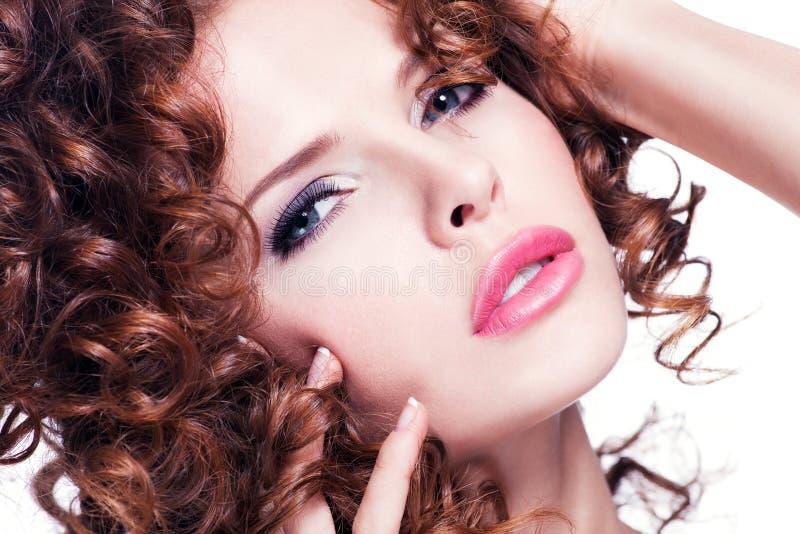 Schönheit mit dem gelockten Haar des Brunette, das am Studio aufwirft lizenzfreies stockfoto