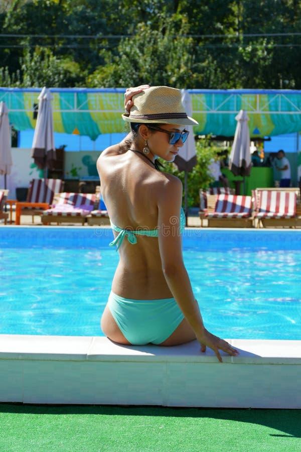 Schönheit mit dem Hut, der durch das Pool sitzt lizenzfreie stockbilder