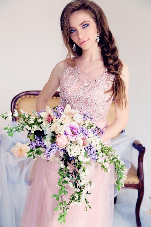 Schönheit mit dem langen dunklen Haar im eleganten Kleid, das unter Blumen aufwirft lizenzfreie stockfotos