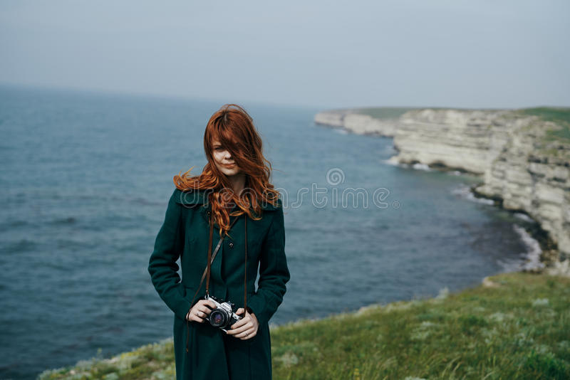 Schönheit mit dem langen roten Haar hält die Kamera am Rand des Berges nahe dem Meer lizenzfreie stockfotos