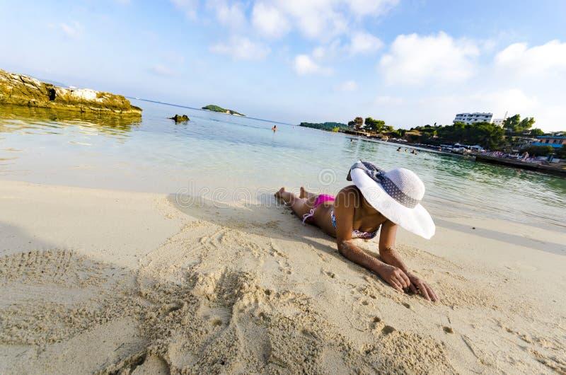 Schönheit mit dem perfekten Körper, der sich auf dem Strand hinlegt stockbilder