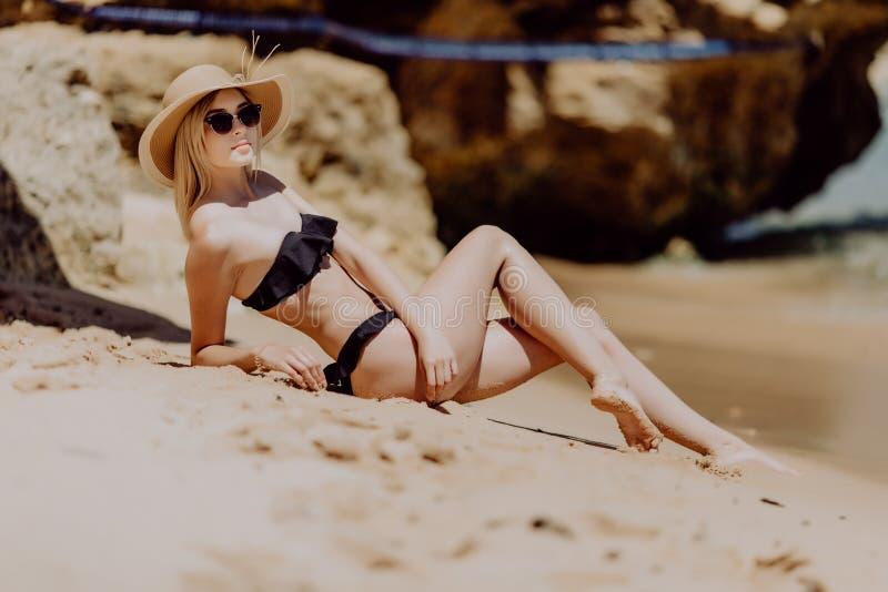 Schönheit mit dem perfekten Körper, der sich auf dem Strand, tragender stilvoller Hut, bräunend auf einem Strandurlaubsort hinleg lizenzfreies stockbild
