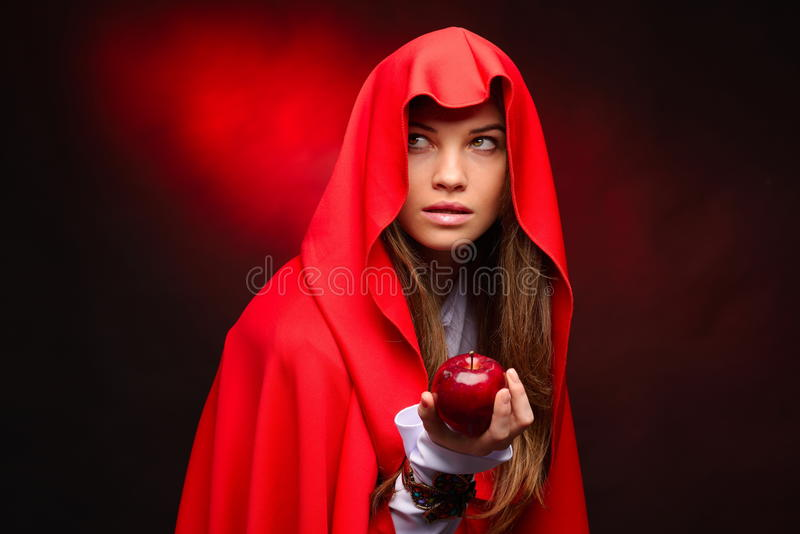 Schönheit mit dem roten Mantel, der Apfel in ihrer Hand hält stockbild