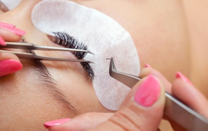 Schönheit mit den langen Wimpern in einem Schönheitssalon Wimper-Erweiterungs-Verfahren stockbild