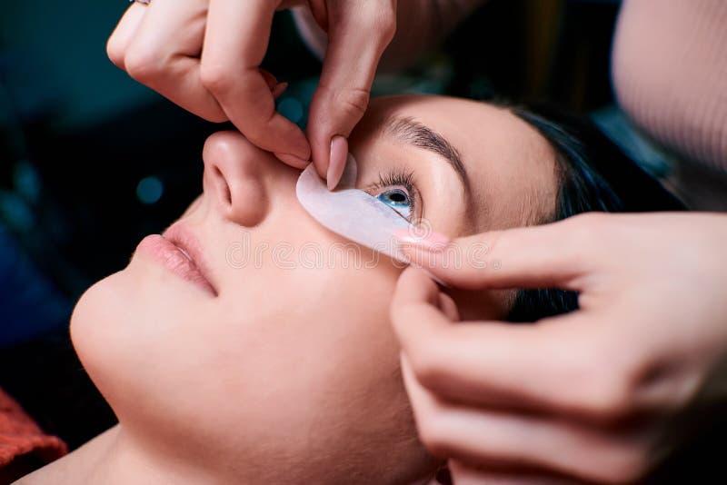 Schönheit mit den langen Wimpern in einem Schönheitssalon Wimper-Erweiterungs-Verfahren Peitschen schließen oben stockfotografie