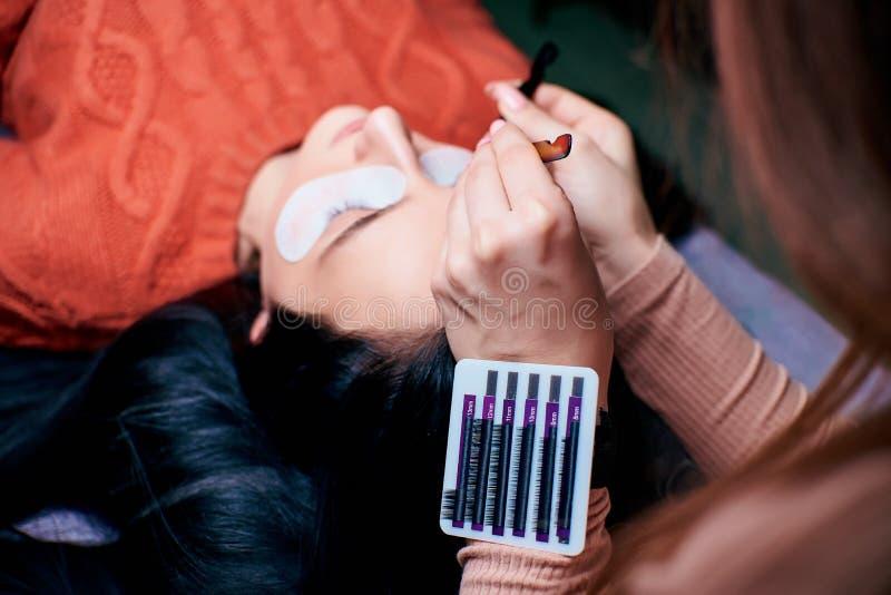 Schönheit mit den langen Wimpern in einem Schönheitssalon Wimper-Erweiterungs-Verfahren Peitschen schließen oben lizenzfreie stockbilder