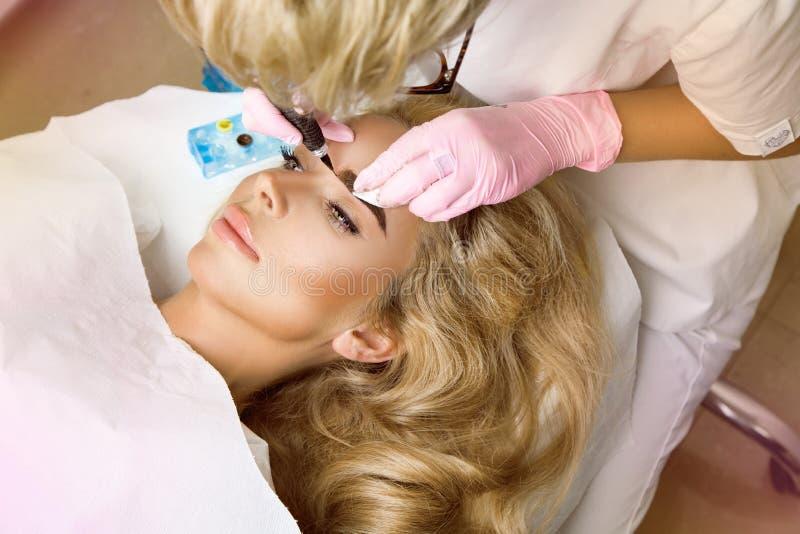 Schönheit mit der glatten, jungen Haut, sitzend in einem Kosmetiker Ein Kosmetiker führt das Modellieren von dauerhaften Augenbra lizenzfreie stockfotos