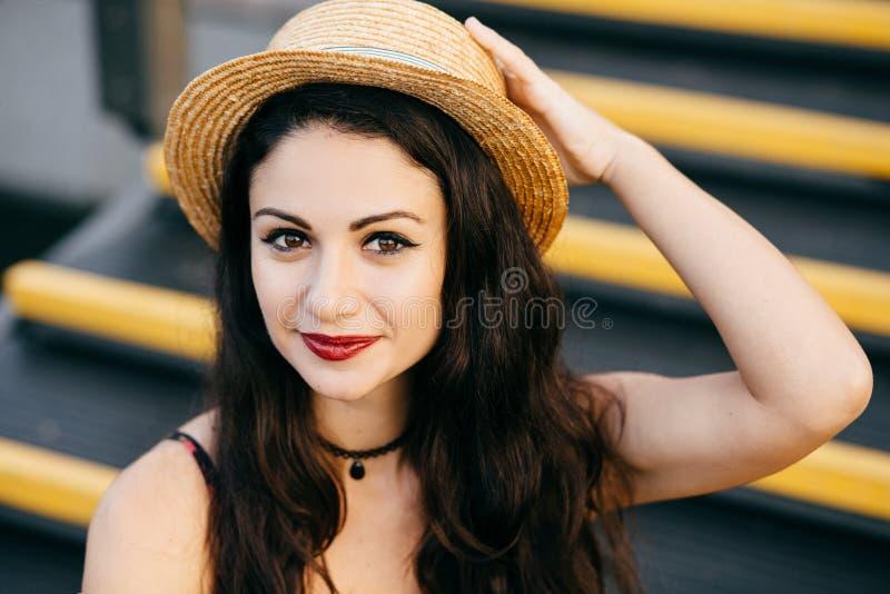 Schönheit mit dunklen Augen und dem Haar, die den tragenden Strohhut des netten Makes-up sitzt an der Treppe hat überzeugten Blic stockbild