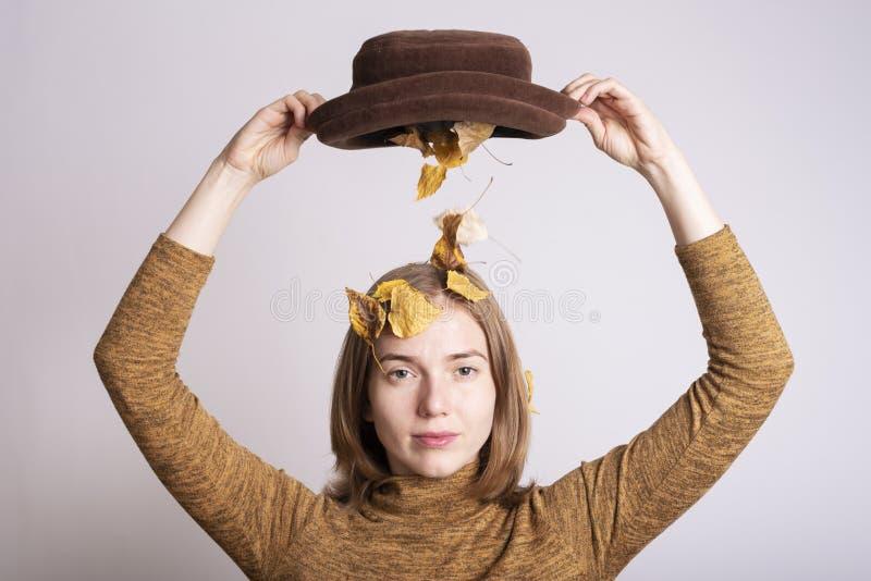 Schönheit mit einem Hut voll vom Herbstlaub lizenzfreie stockbilder