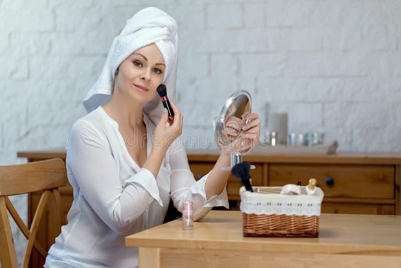 Schönheit mit einem Tuch auf ihrem Kopf, der Make-up tut stockfoto