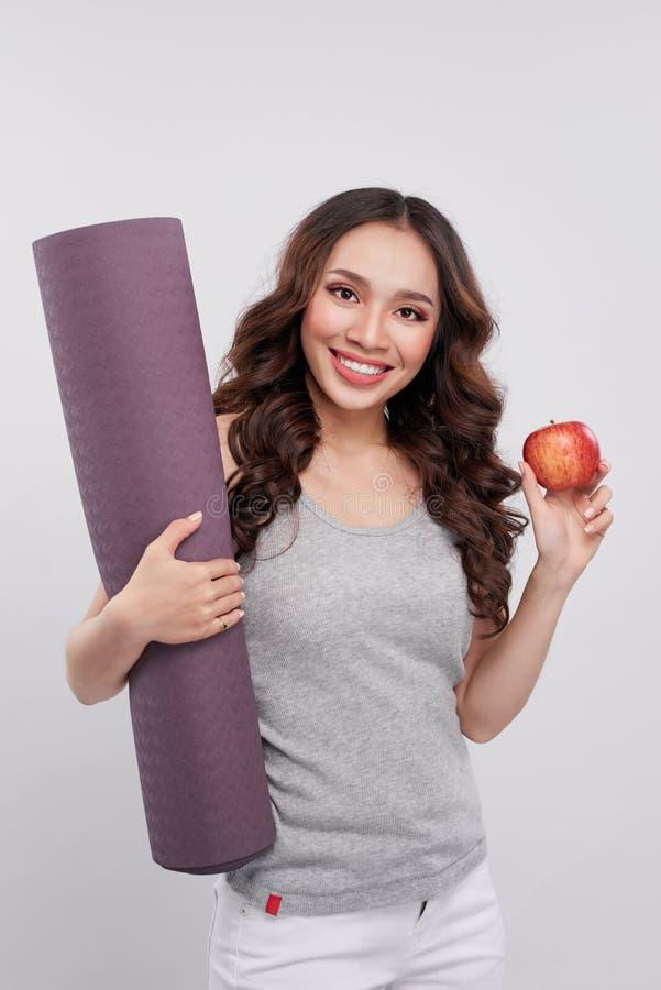 Schönheit mit einer Yogamatte, Hand, die roten Apfel hält stockbilder