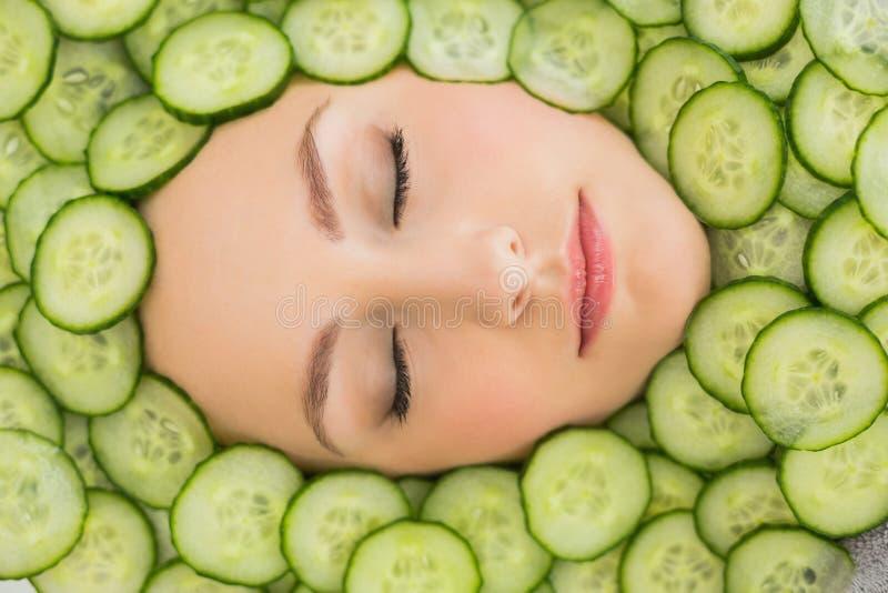 Schönheit mit Gesichtsmaske von Gurkenscheiben auf Gesicht lizenzfreies stockbild