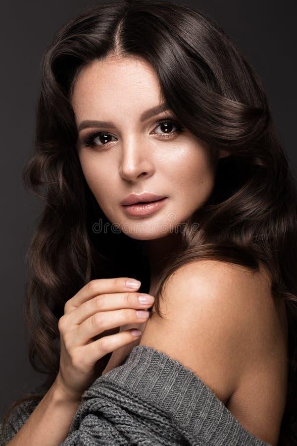 Schönheit mit gesunden Haut und dem Haar kräuselt sich und wirft im Studio auf Schönes lächelndes Mädchen lizenzfreies stockfoto