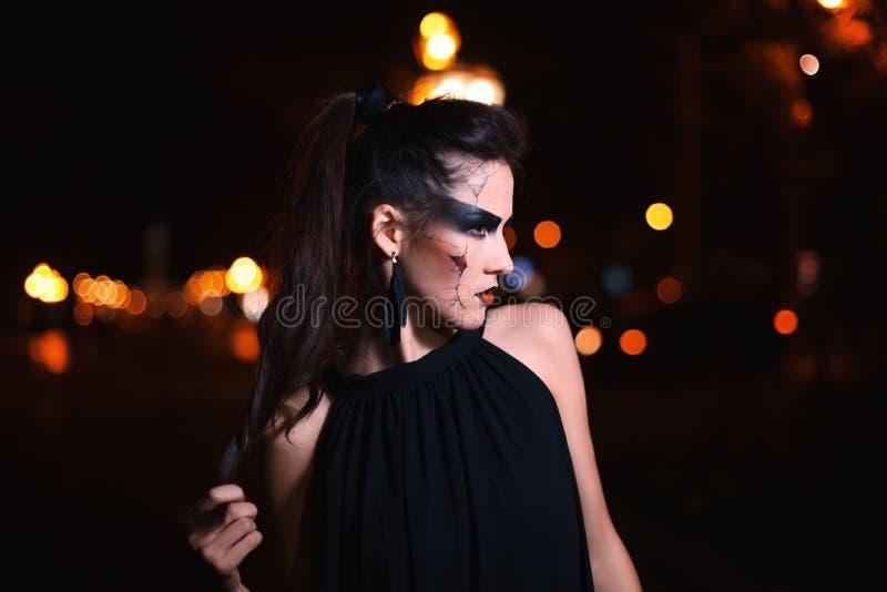 Schönheit mit Halloween-Make-up, das auf der Straße aufwirft Vorbildliches beiseite schauen Abschluss oben Nachtstadthintergrund  lizenzfreie stockfotos