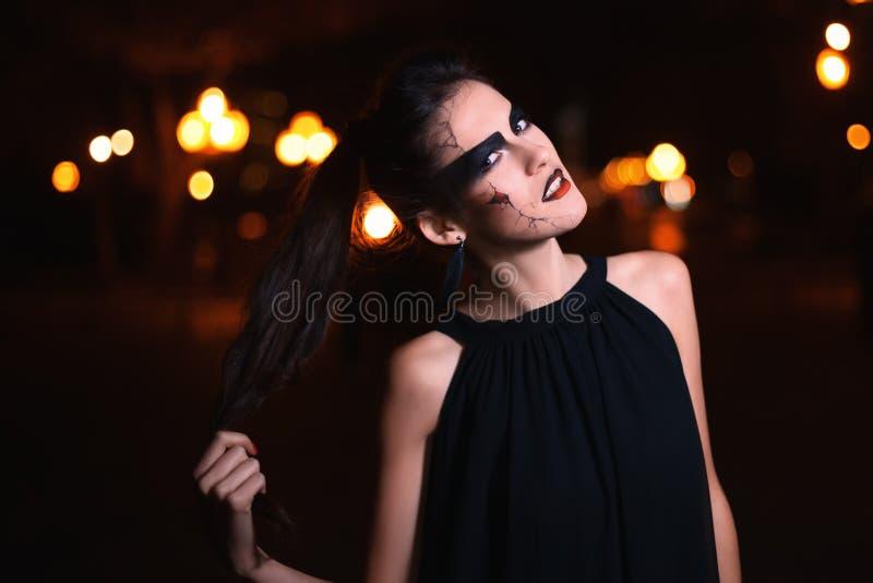 Schönheit mit Halloween-Make-up, das auf der Straße aufwirft Vorbildliches Looking an der Kamera Abschluss oben Nachtstadthinterg lizenzfreies stockbild