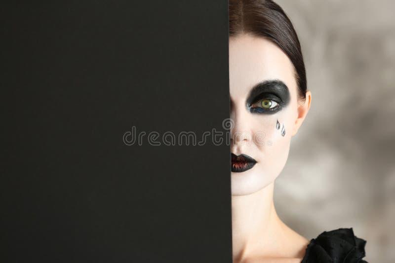 Schönheit mit Halloween-Make-up und Plakat auf grauem Hintergrund lizenzfreie stockfotografie