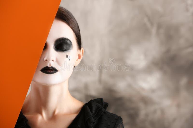Schönheit mit Halloween-Make-up und Plakat auf grauem Hintergrund lizenzfreies stockfoto