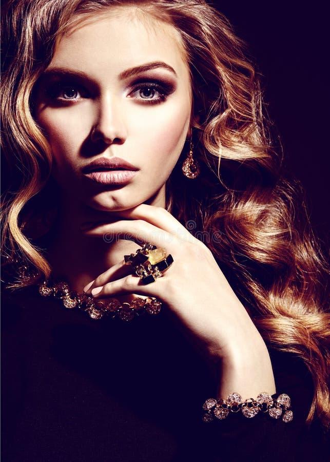 Schönheit mit langem gelocktes Haar- und Goldschmuck stockbilder