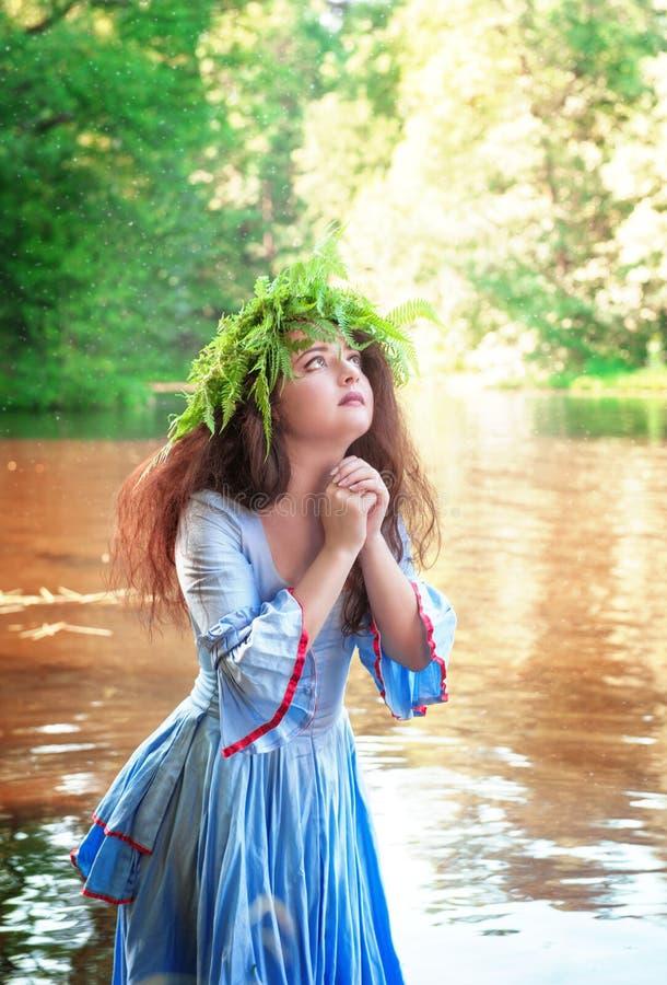 Schönheit mit langem mittelalterlichem Kleid betend im Wasser stockbilder