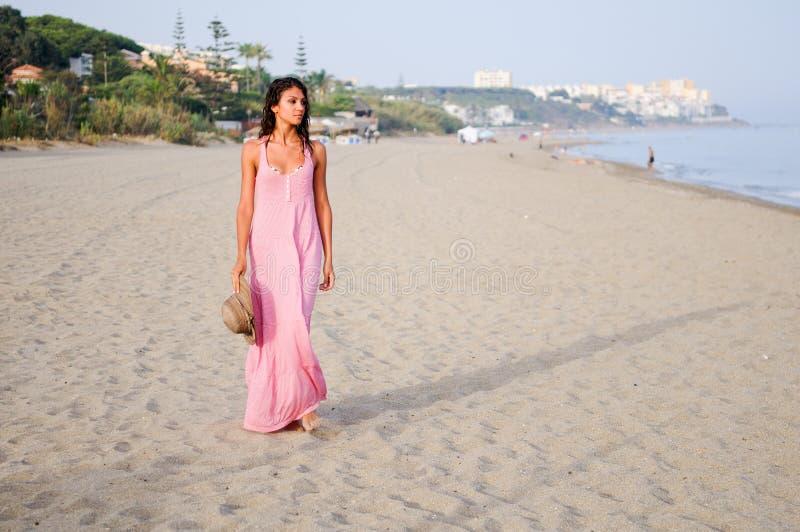 Schönheit mit langem rosa Kleid auf einem tropischen Strand stockbild