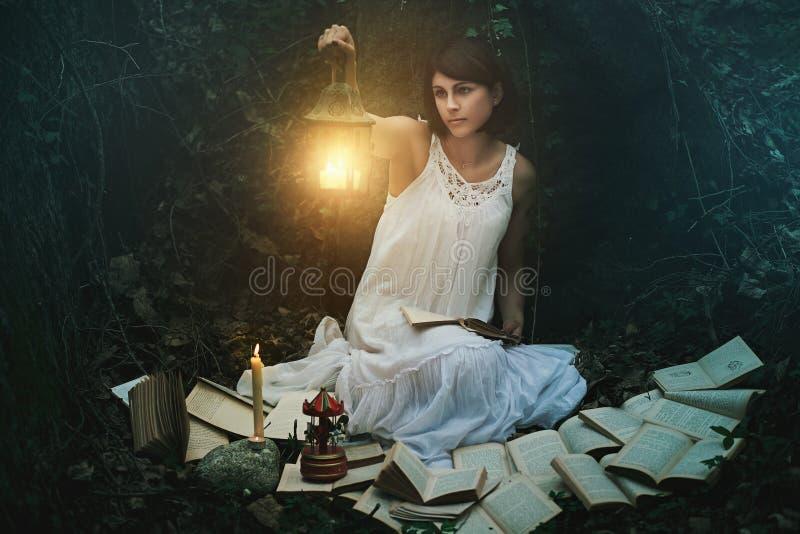 Schönheit mit Laterne in einem dunklen Wald stockfotografie