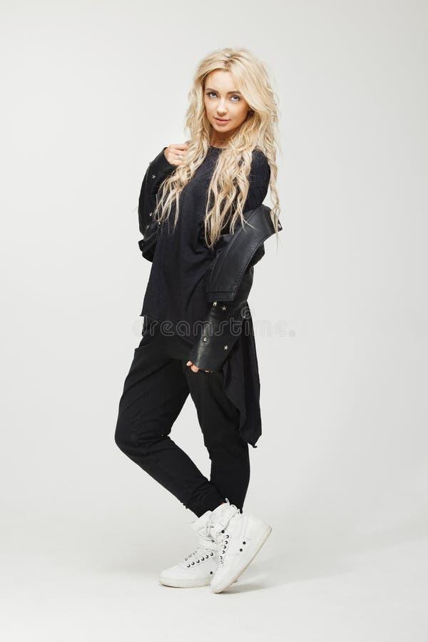 Schönheit mit lond blondem Haar in der stilvollen schwarzen Kleidung am weißen Hintergrund lizenzfreies stockfoto