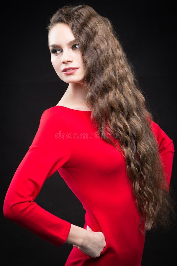 Schönheit mit Make-up des dunklen Haares und des Abends Reizvolles rotes Kleid stockfotos
