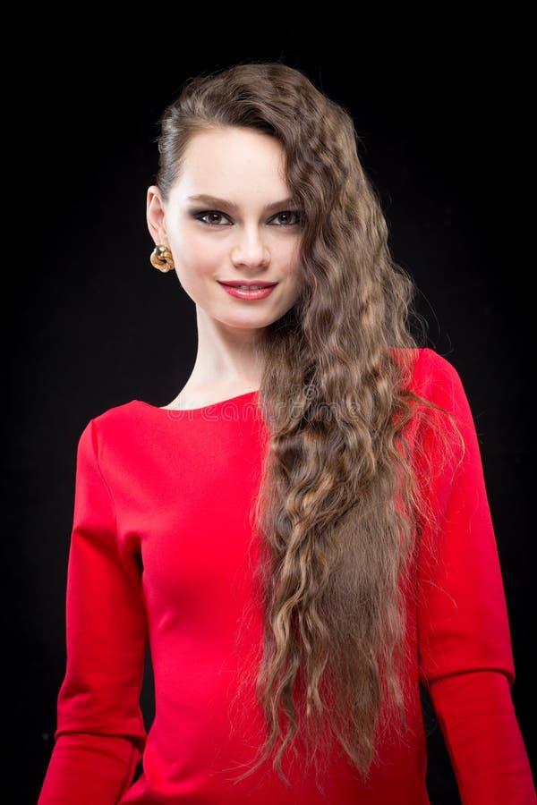 Schönheit mit Make-up des dunklen Haares und des Abends Reizvolles rotes Kleid lizenzfreie stockbilder