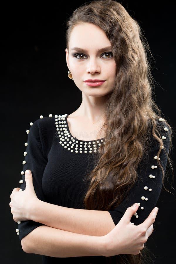Schönheit mit Make-up des dunklen Haares und des Abends Reizvolles schwarzes Kleid stockfotos