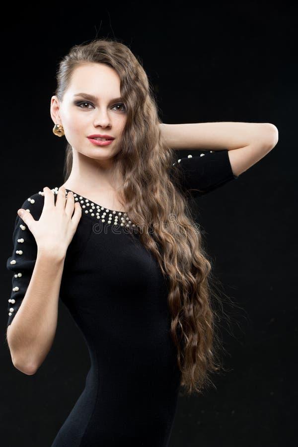 Schönheit mit Make-up des dunklen Haares und des Abends Reizvolles schwarzes Kleid lizenzfreie stockbilder