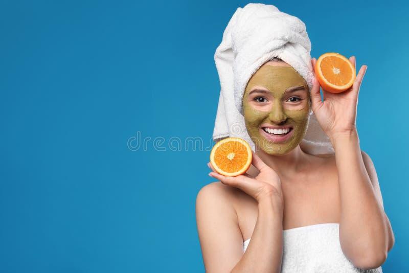 Schönheit mit Maske auf Gesichts- und Schnittorange gegen Farbhintergrund stockbild