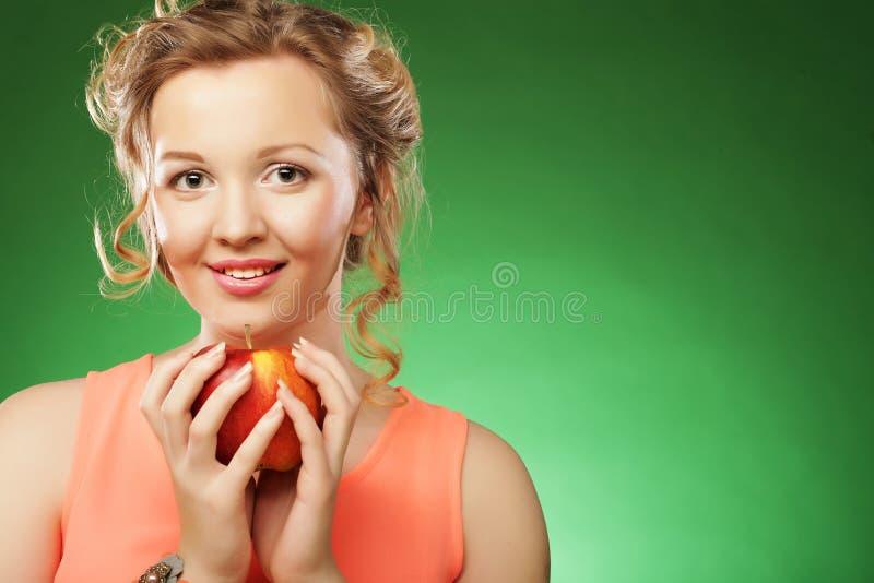 Schönheit mit rotem Apfel in der Hand stockbilder