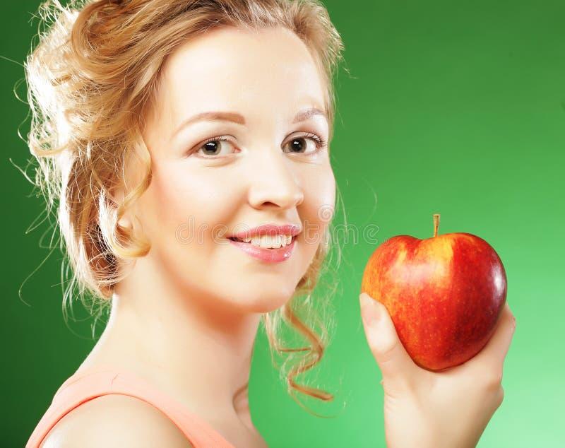 Schönheit mit rotem Apfel in der Hand lizenzfreie stockfotos