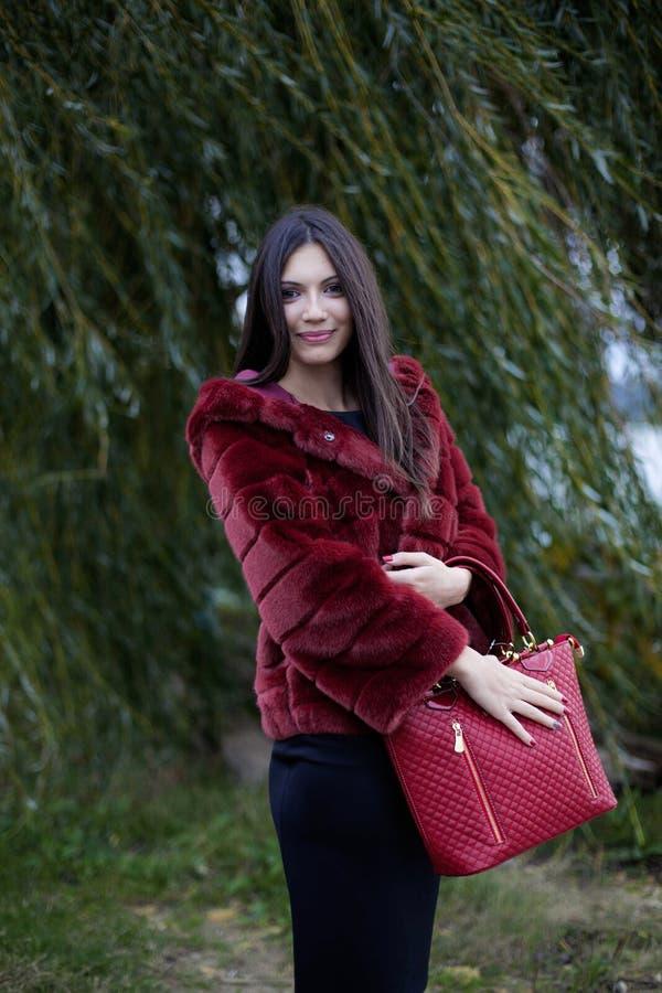 Schönheit mit rotem Mantel und Tasche stockfotos