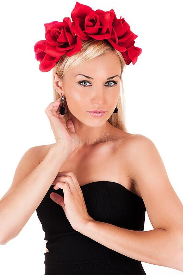 Schönheit mit roten Rosen auf ihrem Kopf stockfotos