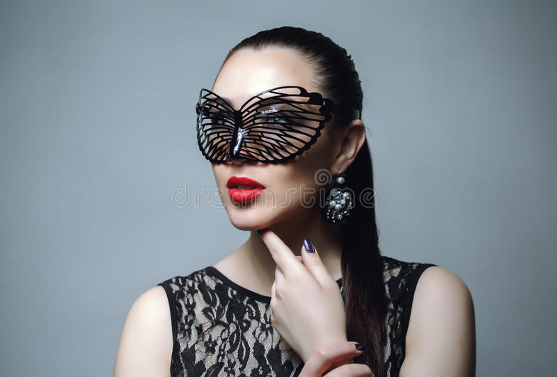 Schönheit mit schwarzer Spitze-Maske über ihren Augen Rote sexy Lippen- und Nagelnahaufnahme lizenzfreie stockfotos