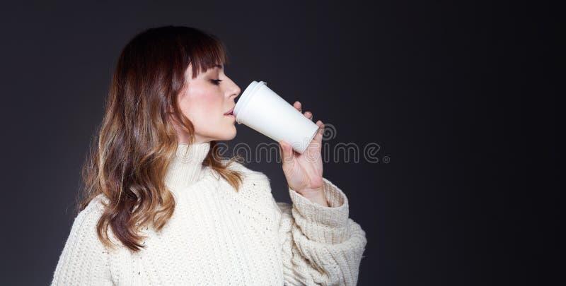 Schönheit mit tragender Strickjacke des langen Haares hält Papierwegwerfkaffeetasse Trinkender Kaffee mit entspanntem Profilgesic lizenzfreie stockfotos