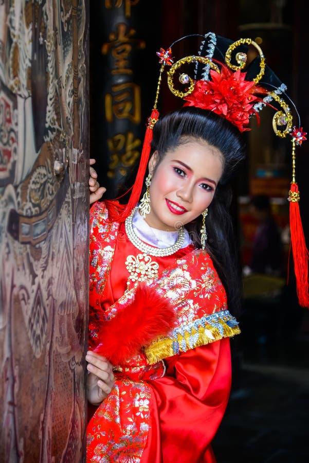 Schönheit mit traitional chinesischem rotem Kleid lizenzfreies stockfoto