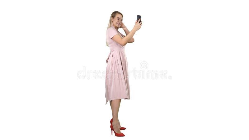 Sch?nheit putzen das Schauen zu ihrem Telefon auf wei?em Hintergrund stockfotografie