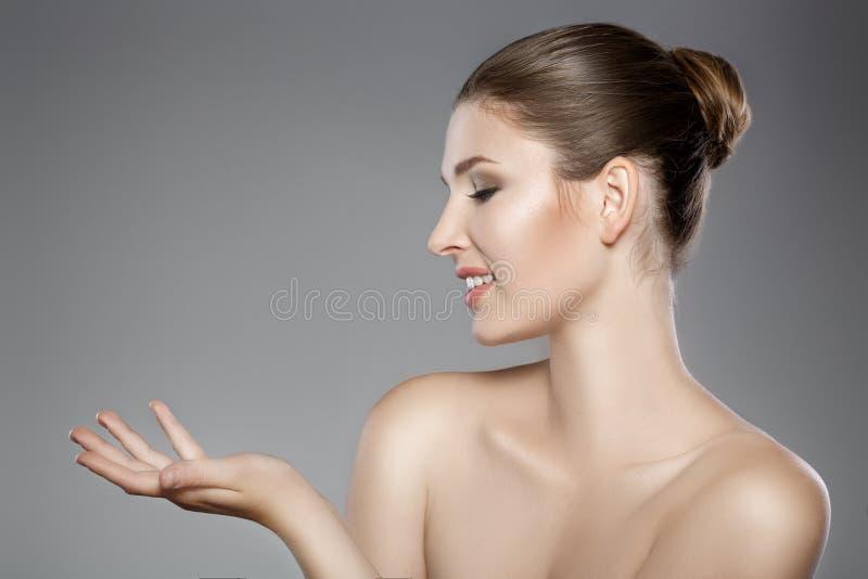 Schönheit ` s Gesicht mit blauen Augen und säubern frische Haut Mädchen zeigt auf etwas stockfotografie