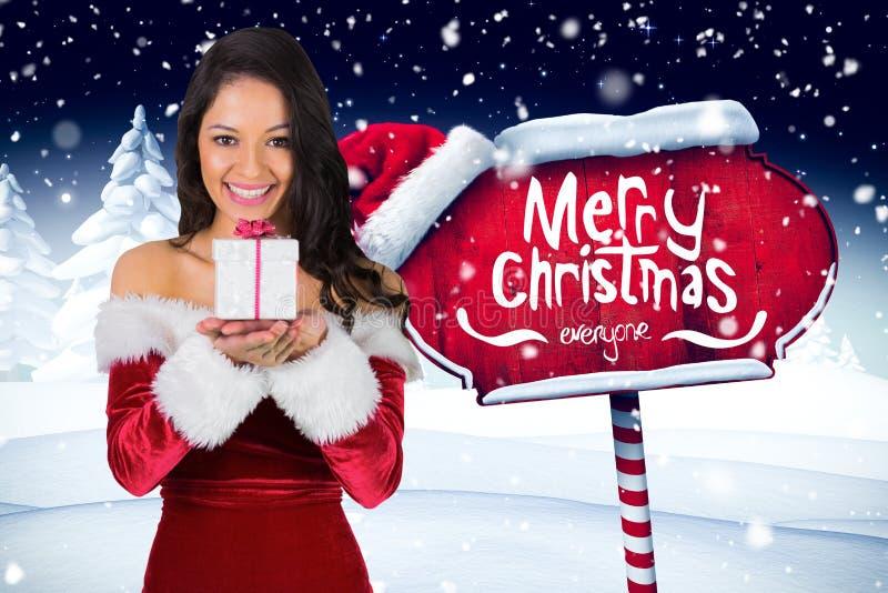 Schönheit in Sankt-Kostüm, das Weihnachtsgeschenk hält stockbild