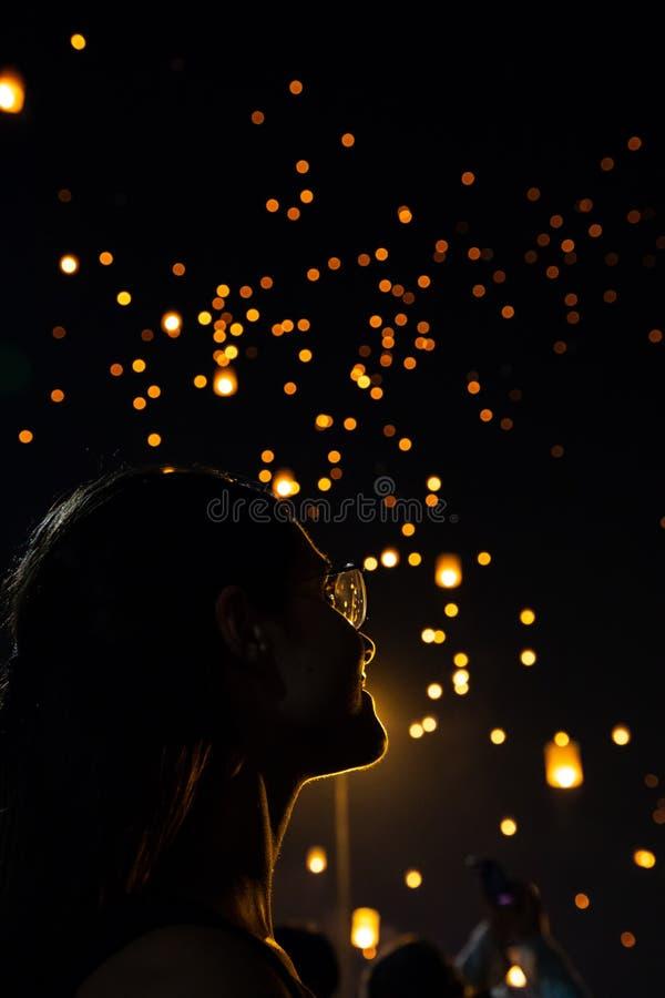 Schönheit silhouett Porträt, das Loy Krathong-Papierlaternen als bokeh auf Hintergrund in Thailand betrachtet stockfotografie